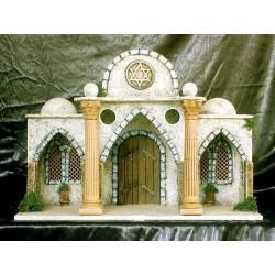 Templo con estancia interior, puerta de fondo y laterales decorados con menorás, la fachada presenta 3 arcos ojivales y fronton