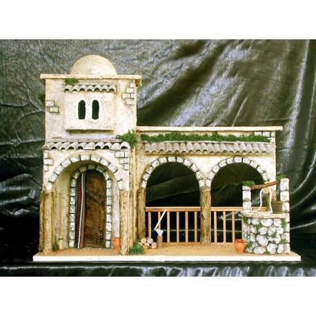 Casa con patio exterior, pozo de agua y arcos de fondo.