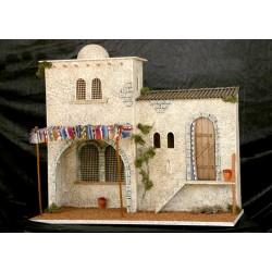 Casa con una estancia interior cubierta por un toldo y otra con puerta y escalera.