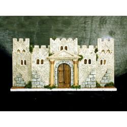 Castillo en relieve con puerta principal, torreones laterales y flanqueado por una muralla.