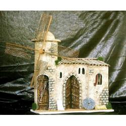 Molino con movimiento, formado por una torre circular donde se encuentran las aspas y una parte central con puerta, ventana y cu